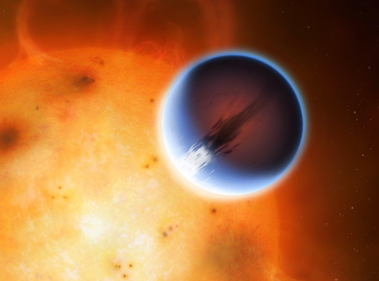 Eksoplaneetan päiväpuoli näkyy kuvituksessa sinertävänä emotähtensä lähellä. Yön ja päivän lämpötilojen erot tuottavat planeetalle huimia tuulia. Kuva: Mark Garlick, University of Warwick