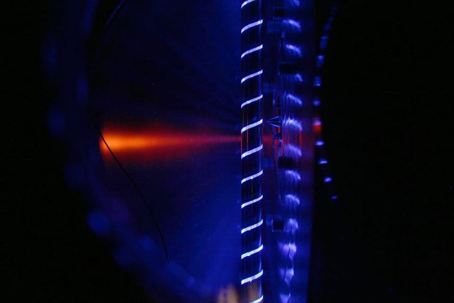 Laserfotolyysi reaktorissa. Putken reiästä poistuvat molekyylit napataan massaspektrometriin kuvassa näkyvästä kartiosta.