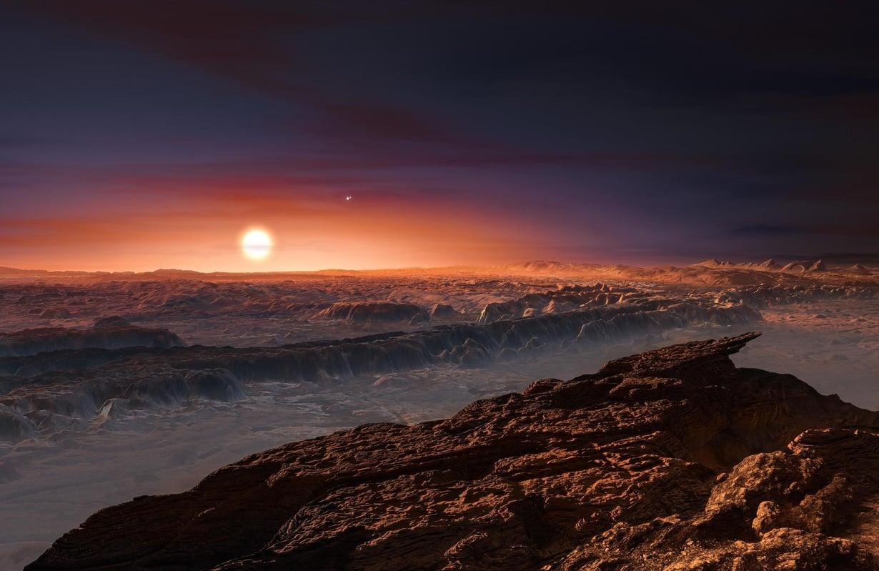 Taiteilijan näkymä lähimmän eksoplaneetan pinnalta. Taivaalla paistaa punainen kääpiötähti Proxima Centauri. Kuvassa näkyy myös kaksoistähti Alfa Centauri AB kahtena pienenä pisteenä. Kuva: ESO/M. Kornmesser
