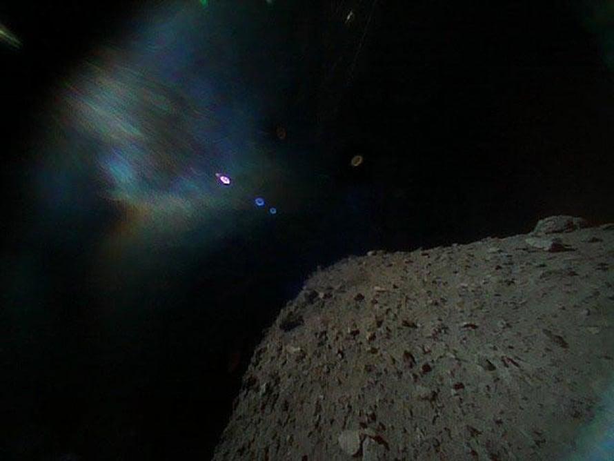 """Robotti on lähtenyt kohti asteroidia, jonka pinta näkyy oikealla. Värikäs sumu johtuu auringon heijastuksista. Kuva: <span class=""""photographer"""">Japan Aerospace Exploration Agency</span>"""