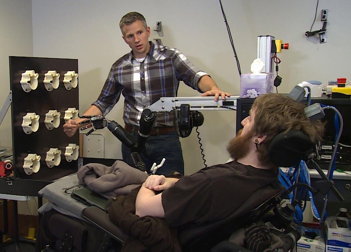 Neliraajahalvaantunut Nathan Copeland (edessä) saa tuntoaistimuksia robottikädestä. Koetta tekee tutkija Rob Gaunt. Kuva: UPMC/Pitt Health Sciences