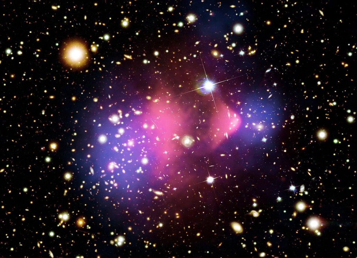Luotijoukko on tunnettu näyttö pimeästä aineesta. Väritetyssä kuvassa näkyy, miten siniset pimeän aineen keskittymät ovat galaksien törmäyksen jälkeen eri paikassa kuin näkyvä aine. Kuva: CHANDRA X-RAY OBSERVATORY CENTER, NASA