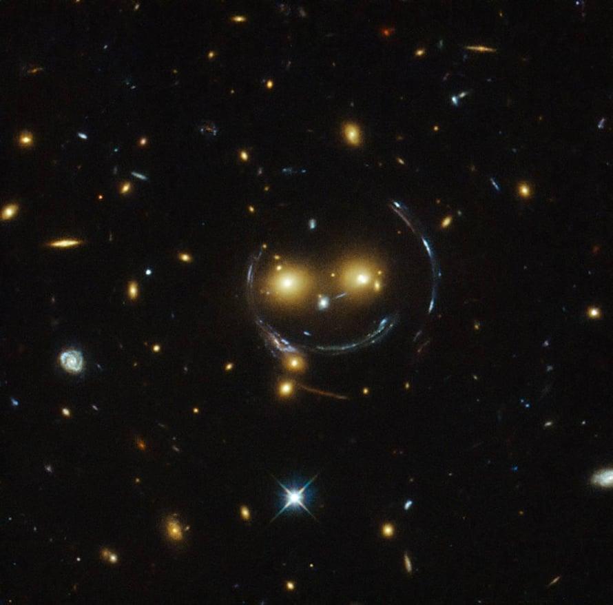Gravitaatiolinssejä on myös kuvattu. Tässä ne muodostavat kaaren ja kuvion, joka näyttää sattumalta ilahduttavasti hymiöltä. Kuva: Nasa
