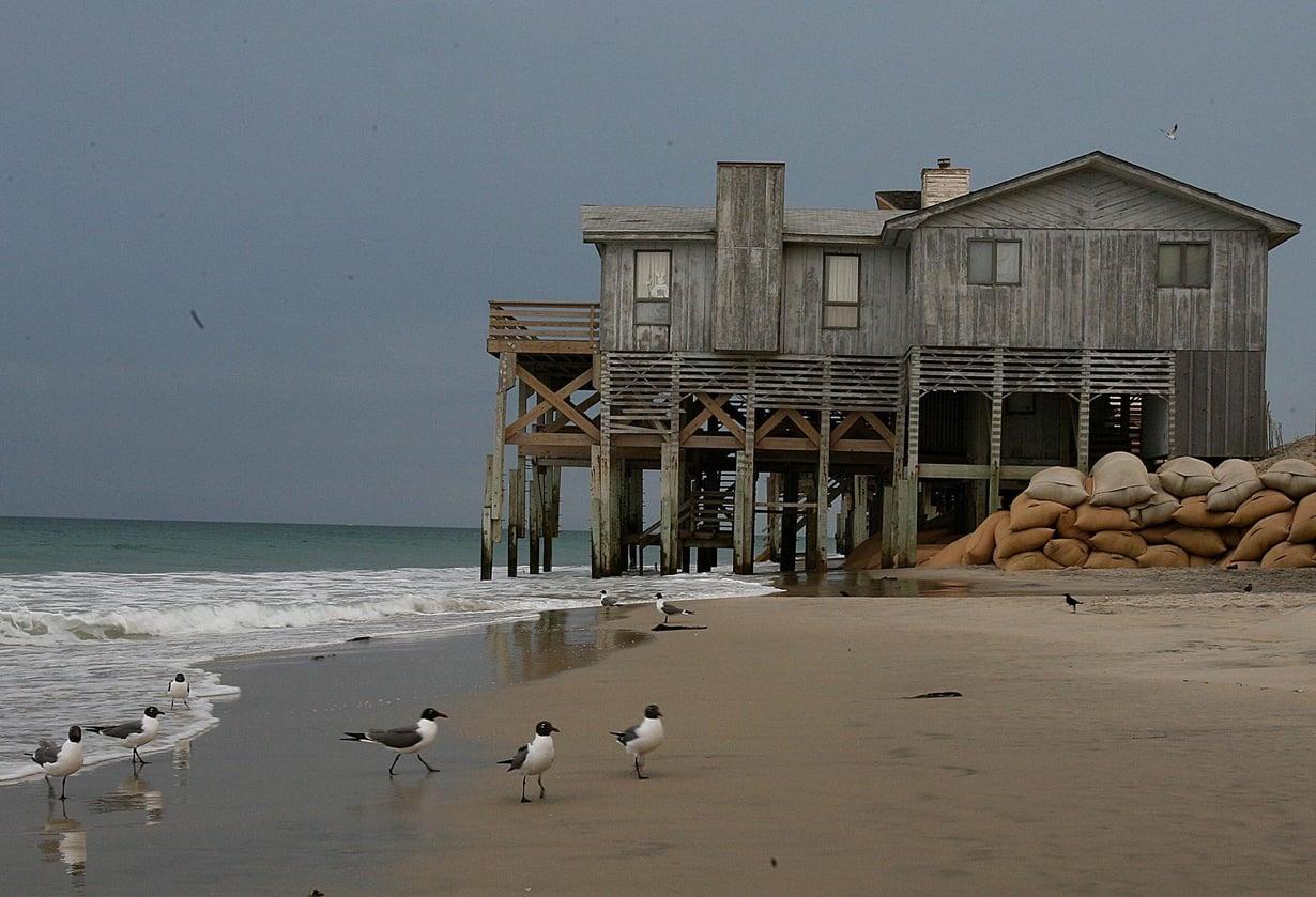Merenpinnan nousu kuluttaa rantaa South Nags Headissa, Pohjois-Carolinan edustan Outer Banks -saarilla. Taloja on yritetty pelastaa jatkamalla tukipylväitä ja kasaamalla hiekkasäkkejä. Kuva: Pekka Mykkänen