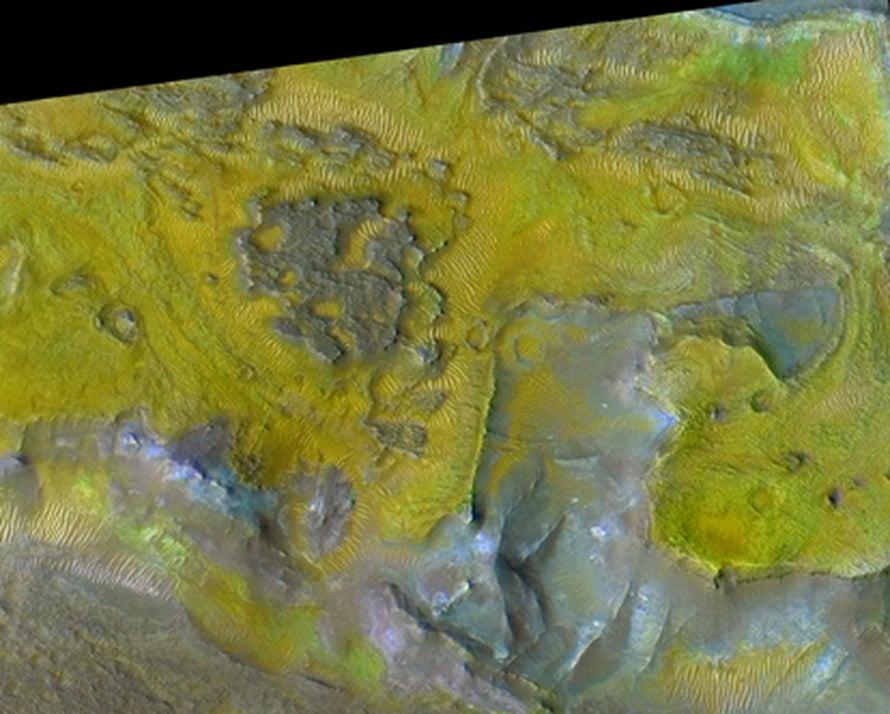 """Lähikuva Marsin Nili Fossaen alueesta. Ylätasankojen (violetti) alapuolella oliviinikerroksia (keltainen), joissa näkyy karbonaattia (kirkas vihreä). Alimmaisena rauta-magnesiumsavea (vaaleansininen). Kuvan alue on läpimitaltaan noin 2,5 km. Kuva: <span class=""""photographer"""">NA</span>"""