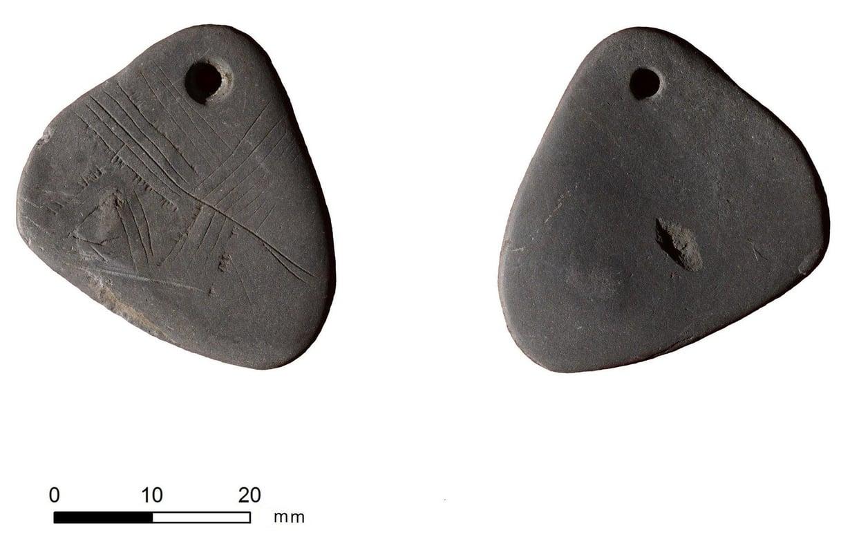 Pieni ja hauras riipus on 11 000 tuhatta vuotta vanha. Tutkijat pohtivat, esittävätkö kaiverrukset ehkäpä puuta. Kuva: Yorkin yliopisto
