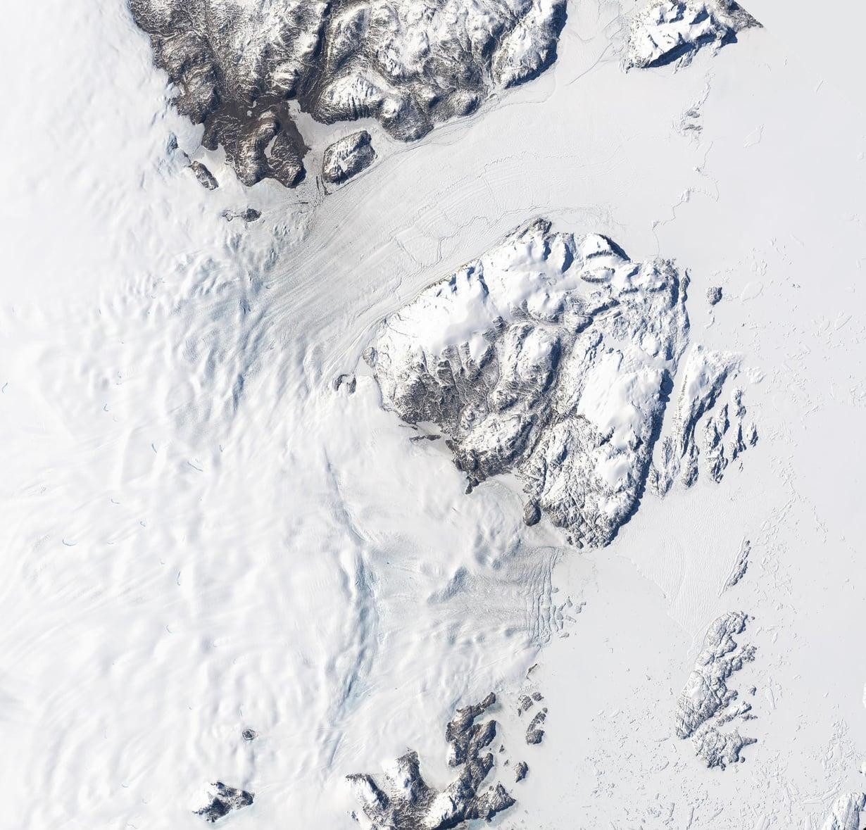 Nioghalvfjerdsfjorden ja Zachariæ Isstrøm vuotavat Atlanttiin. Jäävirroista ylempi kuuluu Nioghalvfjerdsfjordeniin, alempi Zachariæ Isstrømiin. Jäätiköiden vihollinen on sama kuin Etelämantereella: lämpenevä meri. Kuva: Nasa / USGS