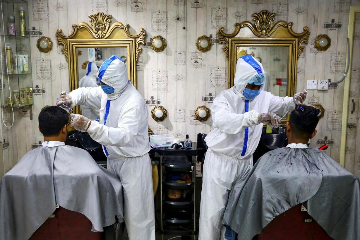 Kasvosuojaimet ovat ilmeisesti estäneet tartuntoja yhdysvaltalaisessa parturi-kampaamossa Yhdysvalloissa. Kuvan parturit työskentelevät Bangladeshissa. Kuva: Mohammad Ponir Hossain / REUTERS