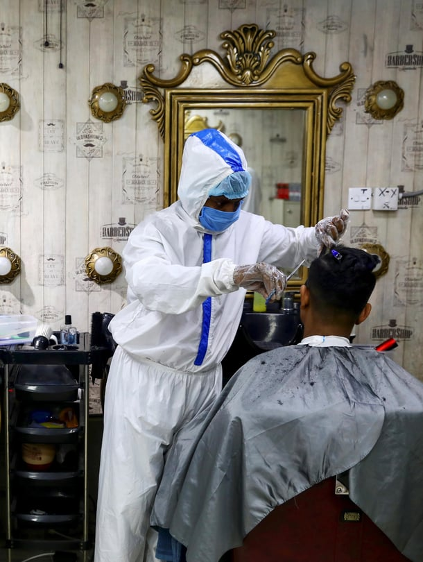 """Kasvosuojaimet ovat ilmeisesti estäneet tartuntoja yhdysvaltalaisessa parturi-kampaamossa Yhdysvalloissa. Kuvan parturit työskentelevät Bangladeshissa. Kuva: <span class=""""photographer"""">Mohammad Ponir Hossain / REUTERS</span>"""