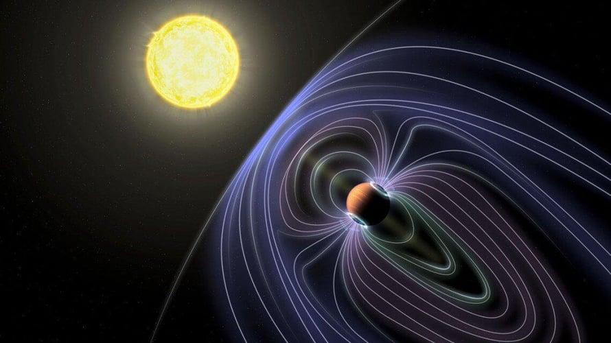 """Taiteijan näkemys Tau Boötes B -järjestelmästä. Siniset viivat kuvaavat planettaa suojaavaa magneettikenttää. Kuva: <span class=""""photographer"""">Jack Madden/Cornell University</span>"""