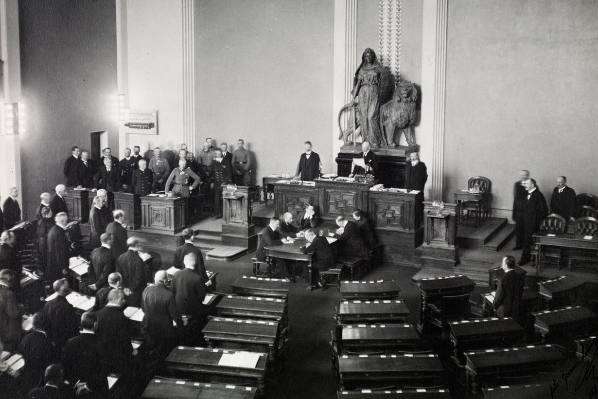 Eduskunnan työ jatkuu 15. toukokuuta. Kenraali von der Goltz seisoo käsi lanteella puhemiehen korokkeen oikealla puolella. Asennosta näkee, kuka on isäntä talossa. Kuva: Museovirasto