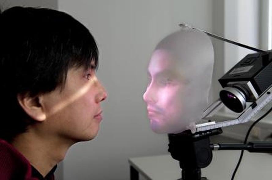 Tutkija Takaaki Kuratate ja robottinaama Mask-bot kasvokkain.