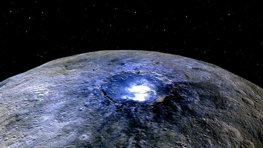 """Occatorin kraatterin vaaleat pisteet hehkuvat kirkkaina vääräväritetyssä kuvassa. Mutta myös luonnollisissa väreissään pilkut heijastavat paljon enemmän valoa kuin muu Cereksen pinta. Kuva: <span class=""""photographer"""">Nasa</span>"""