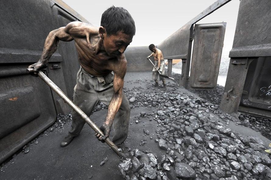 """Kivihiiltä lapioidaan junavaunusta Kiinan Hefeissä. Kuva: <span class=""""photographer"""">Jianan Yu / Reuters</span>"""