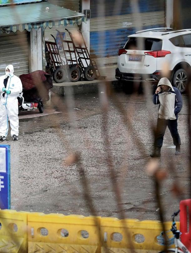 """Suoja-asusteisiin pukeutunut viranomainen Wuhanin kalatorin lähistöllä 10. tammikuuta. Koronaviruksen leviämispaikaksi epäilty tori on ollut suljettu tammikuun alkupuolelta lähtien. Kuva: <span class=""""photographer"""">Darley Shen / Reuters</span>"""