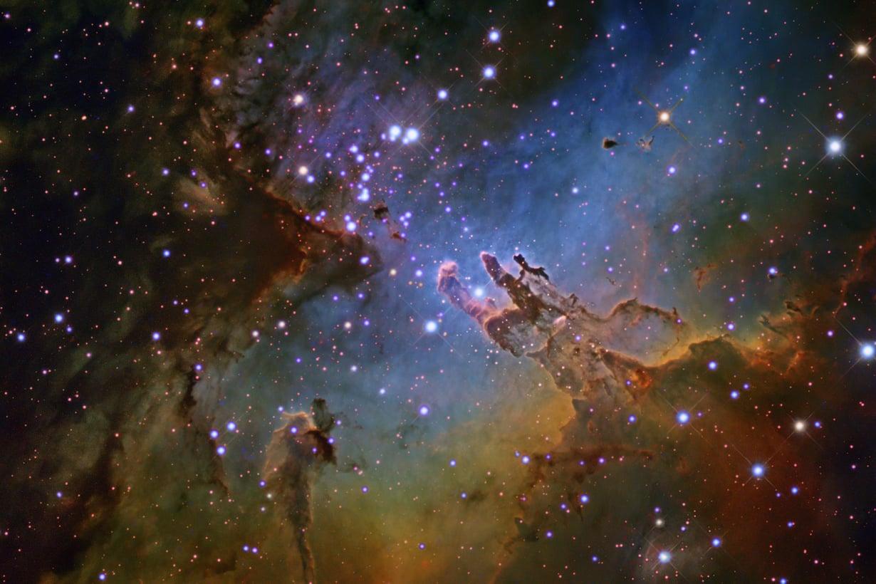 Luomisen pilarit sijaitsevat Käärmeen tähdistön Kotkasumussa. Arkkitehteinä ovat toimineet tähtien ultraviolettisäteily ja voimakkaat tähtituulet. Kuva: SPL/MVPhotos