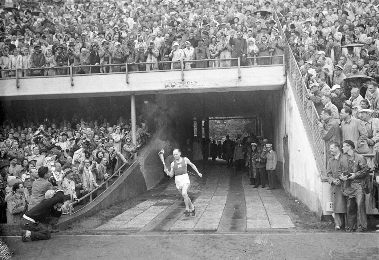 1952 Viimeiseen asti salaisuutena pidetty kotiolympialaisten soihdunkantaja saapuu stadionille. 70 000-päinen yleisö puhkeaa suosionosoituksiin.